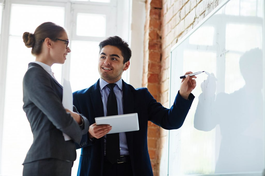 Young economist pointing at whiteboard while explaining statistics to colleague